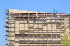 Travaillez travailler au haut échafaudage dans le chantier de construction Photographie stock libre de droits