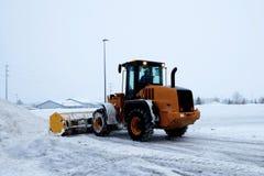 Travaux de chargeur d'embout avant comme machine de déblaiement de neige dégageant un parking images libres de droits