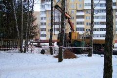 Travaux de construction, la grue de charge-levage d'automobile, flèche de grue de camion dans la perspective des arbres, hiver, l images stock