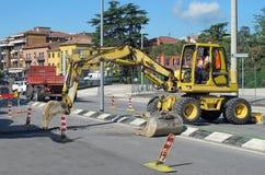 Travaux routiers avec un grattoir à travailler au milieu de la route Photographie stock libre de droits