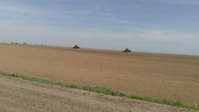 Travaux sur le terrain de ressort sur des tracteurs photos stock