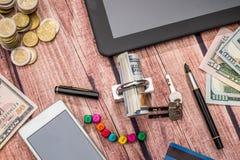 trave, cédula do dólar, moeda, tabuleta e telefone Fotos de Stock