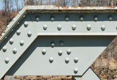 Trave d'acciaio ad angolo con i ribattini su superficie dipinta Immagine Stock