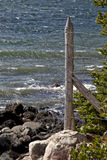 Trave di legno con filo spinato sulla riva rocciosa fotografia stock