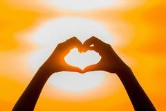 Trave o sol à mão com forma do coração no tempo do por do sol Imagem de Stock