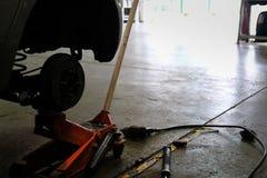 trave pedaços do eixo do cubo do disco & de roda no auto serviço O carro levanta acima FO fotografia de stock