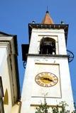 travedonamonate väggen och det kyrkliga tornet sätter en klocka på solig dag Royaltyfri Foto