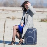 Travel. The woman in grey coat sitting on  suitcase Stock Photo
