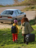 Travel - departure. Mother and little girl (holding hands) with their suitcases go under the car ready to go. Vertical color photo stock photos