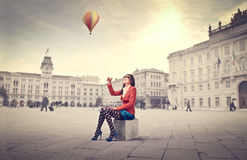 Travel. Smiling beautiful woman sitting on a square with hot-air balloon in the background Stock Photos