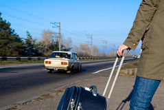 Travel. Woman with suitcase standing at road Royalty Free Stock Photography