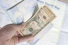Travel. An open passport with dollars inside.  In the background is a metro tourist map. Some words have been removed from the passport, as they could have been Stock Photo