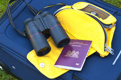 Travel accessories. A blue suitcase laying on the grass with on it binoculairs, a yellow waistbag and a Dutch passport Royalty Free Stock Photo