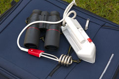 Travel accessories. Like binoculars, travel iron and an immersion heater laying on a blue suitcase Stock Image