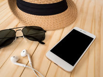 Travel accessories concept. Smartphone, earbuds, sunglasses, hat. Travel accessories concept. Smartphone, earbuds, sunglasses, woven hat on wooden table Stock Photography