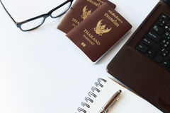 Travel accessories costumes. Passports Thailand, Preparation for travel, Notebook pen on top, glasses, and laptop Royalty Free Stock Image