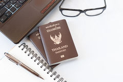 Travel accessories costumes. Passports Thailand, Preparation for travel, Notebook pen on top, glasses, and laptop royalty free stock images