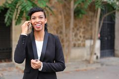 Travel administrator advising tours on smartphone in park. Travel agent talking on smartphone with client and advising cheap tours in park. Pretty female person Royalty Free Stock Photos