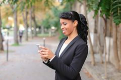 Travel administrator advising tours on smartphone in park. Travel agent talking on smartphone with client and advising cheap tours in park. Pretty female person Royalty Free Stock Images