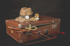 Travel and advanture concept. Vintage brown suitcase with clock, defora hat, bullwhip, compass and ankh key of life on dark backgr. Ound Royalty Free Stock Image
