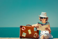 Travel and adventure concept. Child with vintage suitcase and city map on summer vacation. Travel and adventure concept Stock Photography