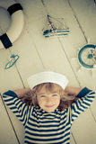 Travel and adventure concept. Happy kid playing with toy sailing boat at home. Travel and adventure concept Royalty Free Stock Photos