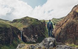 Travel Adventure Concept. Hiking Man Standing On Top Of Cliff In Mountains And Enjoying View Of Nature, Rear View. Young Traveler Man Standing On Top Of Cliff In stock photography