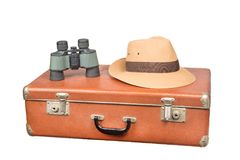 Travel and adventure concept. Vintage brown suitcase with binoculars and fedora hat isolated on white Stock Photography