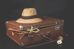 Travel and adventure concept. Vintage brown suitcase with fedora hat, bullwhip, compass and ankh key of life on dark background.  Royalty Free Stock Image