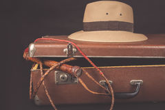 Travel and adventure concept. Vintage brown suitcase with fedora hat and bullwhip on dark Stock Image