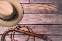 Travel and adventure concept. Vintage fedora hat and bullwhip on wooden table. Top view.  stock images