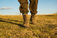 Travel adventure. future. military shoes. male feet in green boots. hynter searching for victim in grass field. going to