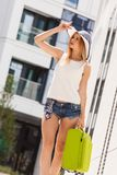 Attractive woman with suitcase walking after arrival. Travel, adventure, teenage journey concept. Walking woman wearing denim shorts, white top and sun hat Royalty Free Stock Image