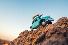 Travel and adventure: toy retro car on rock Royalty Free Stock Photos