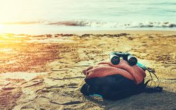 Travel Adventure Concept. Binoculars And Hiking Backpack Lie On The Sunshine Seashore stock image