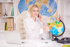 Travel agency. Beautiful travel agent sitting at the table in office and pointing place on globus Royalty Free Stock Photo