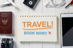 Travel Agency booking Banner with text Travel Book Now on book page. Travel equipment surrounding the Ring Binder with Travel book now message stock photo
