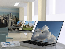 Travel agency concept. With an interior view of the agency with open laptops displaying travel landscapes and one in the foreground with a jetliner exiting the Stock Image