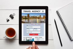 Travel agency concept on tablet screen with office objects. On white wooden table. All screen content is designed by me. Flat lay Stock Photo