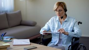 Travel agency consultant in wheelchair searching appropriate tour on tablet. Stock photo royalty free stock images