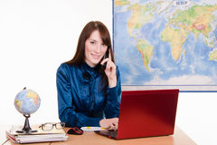 Travel agency employee talking on the phone Stock Image
