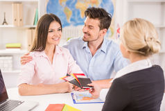 Travel agency. Female travel agent giving tickets to young happy couple Royalty Free Stock Image