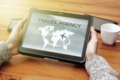 Travel agency. Hands of young by consulting the agency`s travel in internet Stock Photo