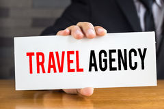 Travel agency, message on white card and hold by Royalty Free Stock Image