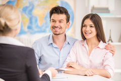 Travel agency. Young happy couple sitting at tourist agency and talking with travel agent Royalty Free Stock Images
