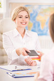 Travel agency. Young pretty travel agent giving tickets to clients Stock Photo