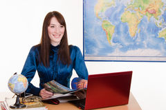 Travel agent flipping through a magazine talking with customers Royalty Free Stock Images