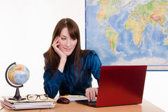 Travel Agent happily looking at a laptop Stock Image
