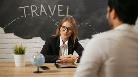 Travel agent has meeting with client. Smiling bright travel agent having meeting with client, attractive young woman talking to handsome bearded man about stock footage