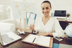 Travel Agent Holding Tickets in Travel Agency. Smiling Woman in Office. Consultant in Travel Office. Airplane Tickets. Modern Office. Holding Tickets in Hand stock photography